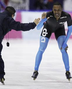 Overall winner Shani Davis, of the U.S., right, high-fives his coach after Davis won the men's 1500-meter speed skating race during the World Cup finals in the Netherlands on Saturday.