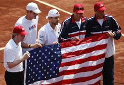 Captain Jim Courier, from left, John Isne, Andy Roddick, Bob Bryan and Mike Bryan got past Chile on Sunday in a first-round Davis Cup match. It was Courier's first appearance as Davis Cup captain.