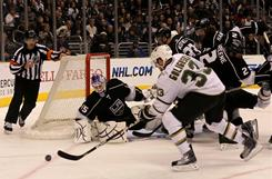 Kings goalie Jonathan Bernier eyes a loose puck as the Stars' Alex Goligoski (33) chases it down at Staples Center. Dallas scored twice in the third period to force OT, then won it on a Brenden Morrow score.
