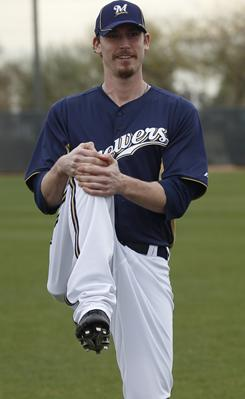 Milwaukee Brewers' John Axford stretches during a spring training baseball workout Friday, Feb. 18, in Phoenix.