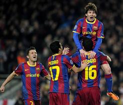 Barcelona teammates lift Lionel Messi after one of his two goals against Arsenal on Tuesday.