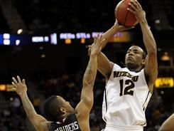 Missouri's Marcus Denmon (12) shoots against Texas Tech's John Roberson during their first-round matchup in the Big 12 tournament. The Tigers held off the Red Raiders 88-84.