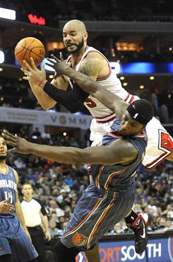 Bulls forward Carlos Boozer, top, flies over Bobcats center Kwame Brown while going after a loose ball during Wednesday's game in Charlotte.