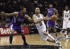 San Antonio guard Tony Parker drives against Sacramento guard Luther Head during the first half on Friday. Parker finished with 27 points and the Spurs beat the Kings 108-103.