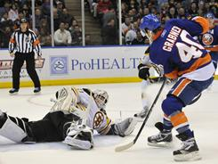 Bruins goalie Tim Thomas blocks a shot by the Islanders' Michael Grabner during the second period on Friday. Grabner scored in the third period and the Islanders won 4-2.