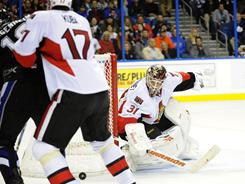 Senators goalie Curtis McElhinney (31) gets help from Filip Kuba (17) while defending the goal against a shot by the Lightning's Sean Bergenheim (10) Friday. Ottawa upset Tampa Bay, winning 2-1.