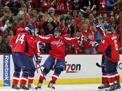 Jason Arnott, left, is mobbed by teammates after scoring a goal Sunday against the Blackhawks. But the Capitals website said he's out week to week with an undisclosed injury.