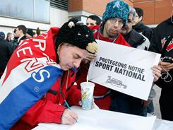 Fans sign a petition asking for the NHL to change rules on head shots before Tuesday's Montreal Canadiens game.