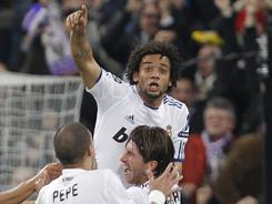 Real Madrid teammates lift Marcelo after his opening goal against Lyon.