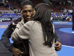 Arizona State's Anthony Robles, born with one leg, gets a kiss from his mom, Judy Robles, after he won the outstanding wrestler award Saturday at the NCAA championships.