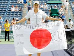 Caroline Wozniacki of Denmark holds a flag dedicated to the people of Japan after advancing past Victoria Azarenka of Russia during the BNP Paribas Open in Indian Wells, Calif. Azarenka retired with an injury.