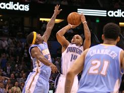 Orlando's Jameer Nelson (14) shoots the game-winning three pointer as Denver's Ty Lawson (3) defends the play. Nelson scored 13 points in the Magic's 85-82 win over the Nuggets.