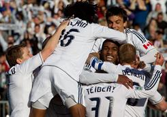 Vancouver Whitecaps' Atiba Harris is mobbed by his teammates after scoring against the Toronto FC during the second half of their MLS game in Vancouver, British Columbia.