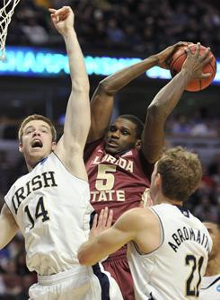 Florida State forward Bernard James collects a rebound between Notre Dame guard Scott Martin (14) and forward Tim Abromaitis during their NCAA tournament third-round game in Chicago.