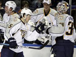 Nashville Predators' Blake Geoffrion celebrates his third goal with goalie Anders Lindback, who had been pulled for an extra skater.
