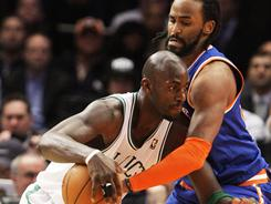 The Celtics'  Kevin Garnett protects the ball from the Knicks' Ronny Turiaf during the first half of on Monday. Garnett finished with 24 points, and the Celtics beat the Knicks 96-86.