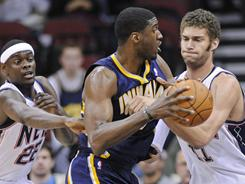 The Pacers' Roy Hibbert is pressured by the Nets' Brook Lopez, right, and Anthony Morrow during the first quarter on Monday. Hibbert finished with 24 points as the Pacers beat the Nets 102-98.
