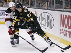 Bruins center Chris Kelly, right, looks to fend off Devils defenseman Henrik Tallinder as the two vie for the puck during the second period Tuesday night.