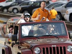 People drive down a street on the University of Tennessee campus with a likeness of former head basketball coach Bruce Pearl on Monday, Tennessee fired Pearl after a season that saw the coach charged with unethical conduct for lying to NCAA investigators during a probe into recruiting.