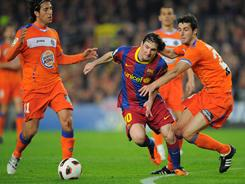 Barcelona star Lionel Messi maneuvers through the Getafe defense during a Spanish league game on March 19.