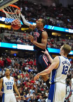 Arizona forward Derrick Williams throws down two of his 32 points as Duke's Kyle Singler looks on during the Wildcats' 93-77 win on Thursday night.