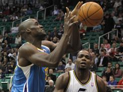 Hornets center Emeka Okafor, left, fumbles the ball as Jazz forward Paul Millsap looks on during the first half of their game Thursday night in Salt Lake City.