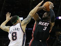 The Heat's Dwayne Wade, shooting over the Nets' Deron Williams, scored 18 points Sunday despite missing part of the game with a thigh injury. Miami beat New Jersey 108-94.