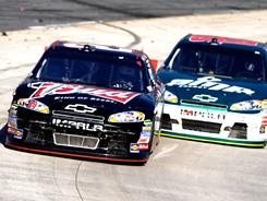 Kevin Harvick takes the lead from Dale Earnhardt Jr. in Sunday's NASCAR race at Martisnville, VA.