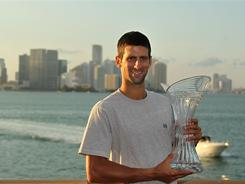 Novak Djokovic of Serbia, showing off the spoils of his latest victory, is on an incredible 24-0 winning streak, including four titles, to begin the season.