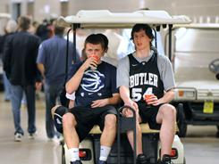 Butler players Chase Stigall, left, and Matt Howard are escorted Sunday to interview rooms, where they were interviewed about their preparation for Monday's championship game against Connecticut.