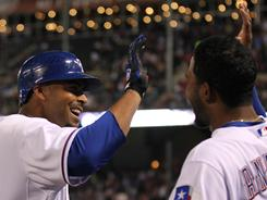 Rangers teammates Nelson Cruz, left, and Elvis Andrus celebrate the former's fourth-inning home run. Cruz has hit four in four games while Andrus added his first of the season in Texas' 6-4 win against the Mariners on Monday.