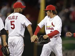 Albert Pujols (5) celebrates with teammate Colby Rasmus (28) and others after the Cardinals beat the Pirates 3-2 on Tuesday. Pujols had two RBI in St. Louis' win.