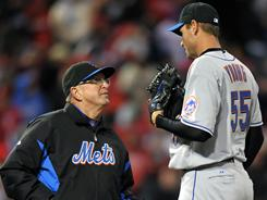 Mets pitching coach Dan Warthen, left, talks to starter Chris Young during their game against the Phillies. Young pitched into the sixth inning and had three hits in New York's win.