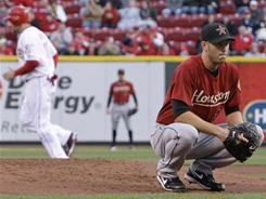Astros starter J.A. Happ, right, squats on the mound after walking the Reds' Chris Heisey (not pictured) with the bases loaded in the first inning. Heisey had three RBI in Cincinnati's win.