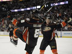 Teemu Selanne, left, and Jason Blake celebrate the first of Selanne's two goals that helped the Ducks clinch a playoff spot.
