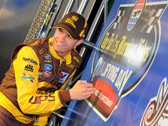 David Ragan signs the pole board in victory lane after claiming the top spot in qualifying for Saturday's Sprint Cup race at Texas Motor Speedway.