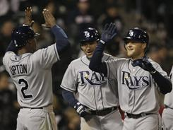 B.J. Upton, left, and Johnny Damon, center congratulate Dan Johnson after Johnson's three-run, ninth-inning home put the Rays ahead for good in their first win of the season.