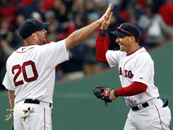 Kevin Youkilis, left, and Marco Scutaro celebrate the Red Sox's first victory of the season.