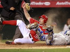 The Angels' Peter Bourjos beats the tag of Blue Jays catcher J.P. Arencibia to score the winning run in the 14th inning of Saturday night's game. The Angels won 6-5.