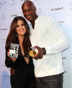 "Khloe Kardashian Odom, left, and Lamar Odom pose for photographers during the ""Unbreakable"" Fragrance Launch at The Redbury in Los Angeles."