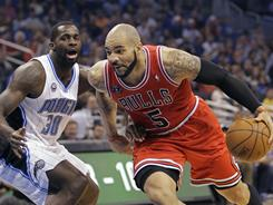 The Bulls' Carlos Boozer, right, driving around the Magic's Brandon Bass, tallied 12 points, six rebounds and six assists in Chicago's 102-99 win.
