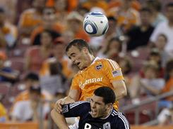 The Houston Dynamo's Cam Weaver goes up for a header over the Vancouver Whitecaps' Michael Boxall during the Dynamo's 3-1 win. 