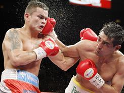 Erik Morales throws a right hand that connects to the jaw of Marcos Maidana during their WBA interim junior welterweight title fight Saturday. Maidana won by majority decision.