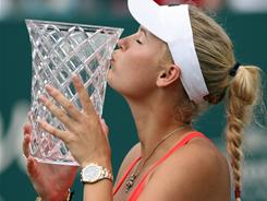 Caroline Wozniacki kisses the championship trophy after her victory over Elena Vesnina in the final of the Family Circle Cup.