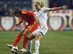 Heather Mitts (right) of the United States puts the pressure on Gu Yasha of China at PPL Park on Oct. 6, in Chester, Penn.