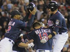 Danny Valencia, center, is mobbed by Twins teammates after his walk-off RBI single vs. the Royals on Tuesday.