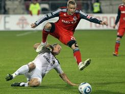 Gianluca Zavarise, above, of Toronto FC jumps over Chad Barrett of Los Angeles Galaxy during their scoreless game on Wednesday night in Toronto.
