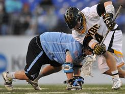 Johns Hopkins' Matt Dolente, left, winning a faceoff March 12 against Neil Lewnes of Maryland-Baltimore County, leads the nation this season, entering the week winning draws at a 70.2% clip.