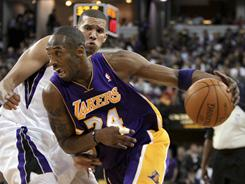 Los Angles Lakers guard Kobe Bryant, drives to the basket past Sacramento Kings forward Francisco Garcia during their game Wednesday night in Sacramento