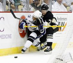Tampa Bay Lightning right wing Martin St. Louis, left, and Pittsburgh Penguins defender Paul Martin (7) chase a loose puck during Game 1 of the Eastern Conference quarterfinals.